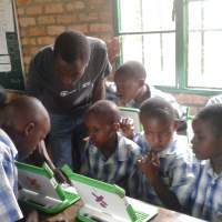 ICS volunteer Fidele teaches a class to code.