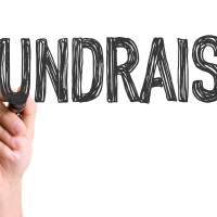 A hand writing the word fundraise.