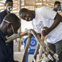 Kwabena Danso, founder of Challenges Worldwide-supported business Booomers Bikes with his employees