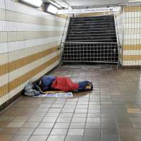 A homeless man sleeps on the floor of a London Underground station
