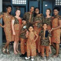 Volunteers stand outside a house in matching patterned clothing