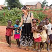 A white woman is accompanied by 6 African children