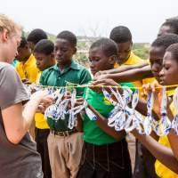 group of children stood attaching bands to a washing line with a volunteer