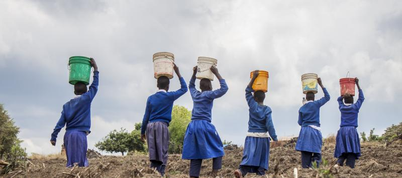 young girls carrying water on their heads