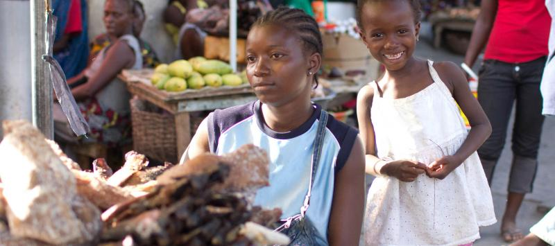A woman and young child stand by food stalls at a market in Monrovia
