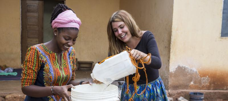 VSO ICS volunteers Francisca Mlingwa and Josie Kearney gather water for cooking