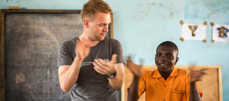 International Service volunteer Frankie teaches a disabled child at Yumba Special School
