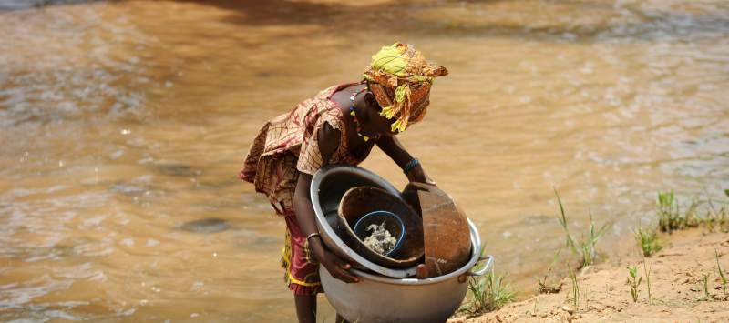 A Burkinabe woman works by the river