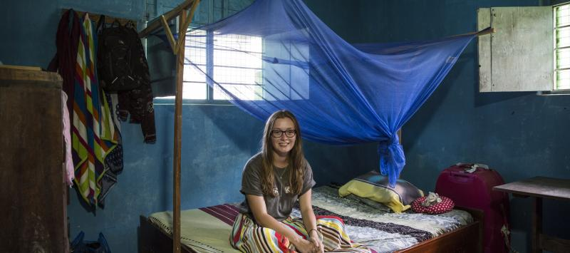 VSO ICS volunteer Rebecca Hastie sitting on her bed in her host home.