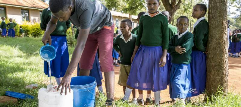 ICS volunteers demonstrate how to filter water through material at Endagikot School, Mbulu, Tanzania