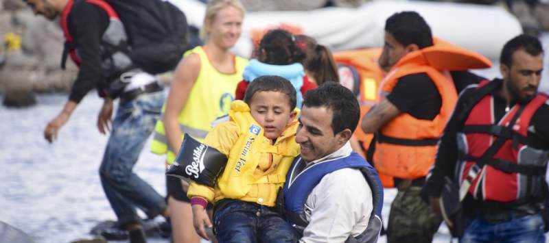 Syrian refugees are helped, by Norwegian volunteers, to land their boat near Molyvos