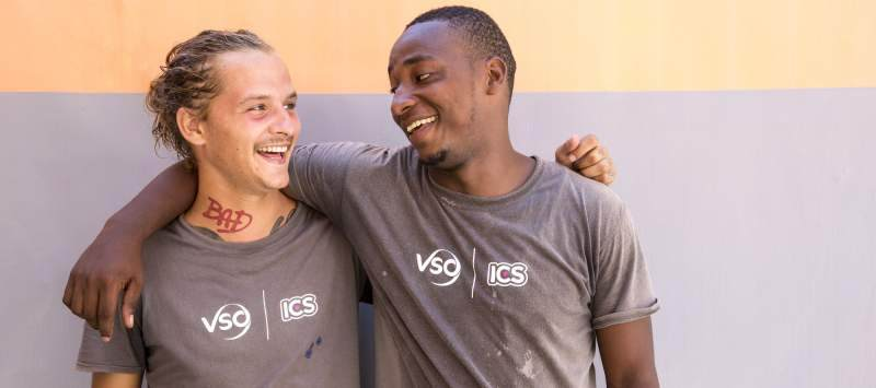 Izak laughs with his counterpart Nasir as they prepare for a community action day