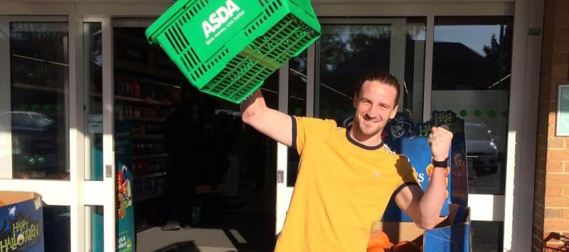 Man outside supermarket holding basket in air