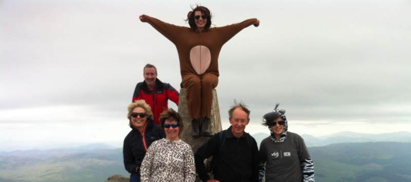 Volunteer with family and friends all in fancy dress at the top of a mountain for their sponsored challenge