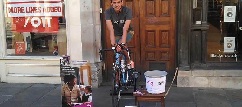 A volunteer sat on a bike completing a sponsored challenged in the middle of the high street.