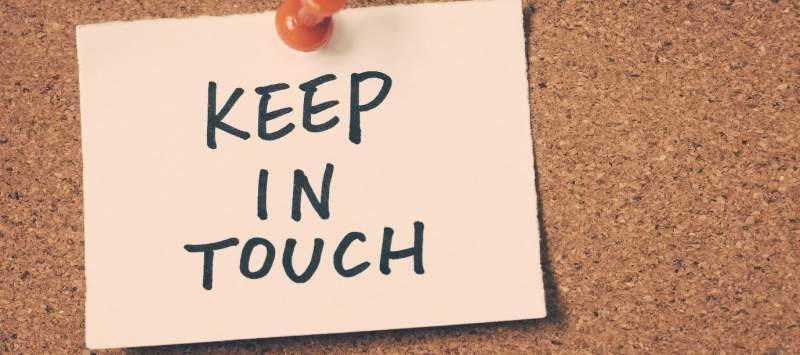 Keep in touch, written on a post it note and pinned to a cork board.