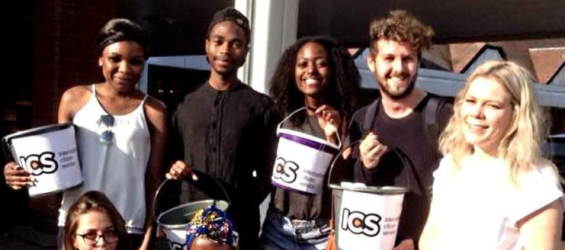 A group of volunteers all holding ICS buckets before a bucket collection