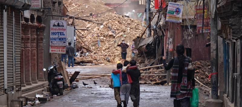 Three boys watch ongoing rescue work on a collapsed building in Kathmandu