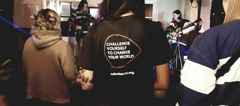 Volunteer standing at a gig wearing an ICS t-shirt which says, 'challenge yourself to change the world'.