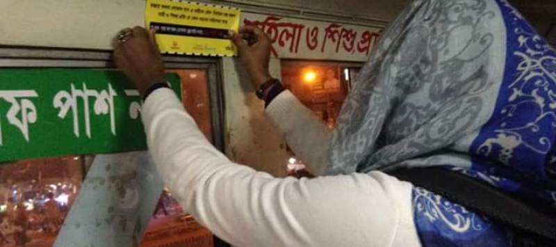 A NYEN Bangladesh member puts up a sticker advising women about a helpline for harassment