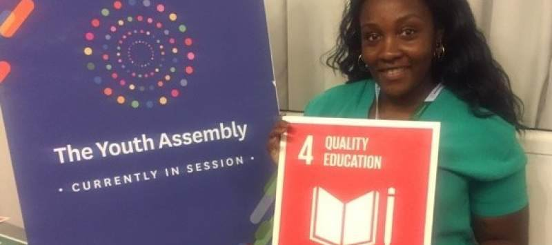 Sarah holds up the sign for SDG 4 - access to quality education