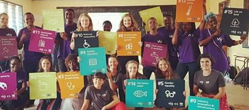 UK and Tanazanian volunteers hold up brightly coloured SDG signs