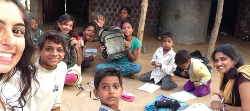 A group of Indian children sit with schoolbags around them