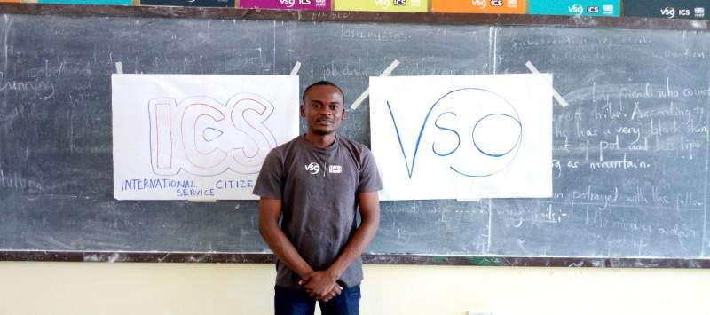 Tanzanian project officer Nicholaus stands by a blackboard