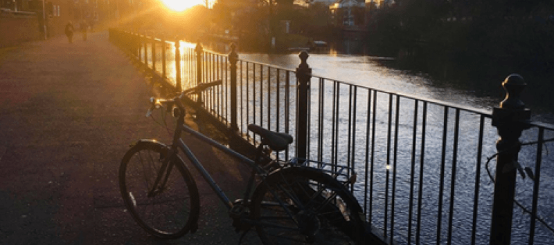 Photo of Alex's bike next to the river at sunset.