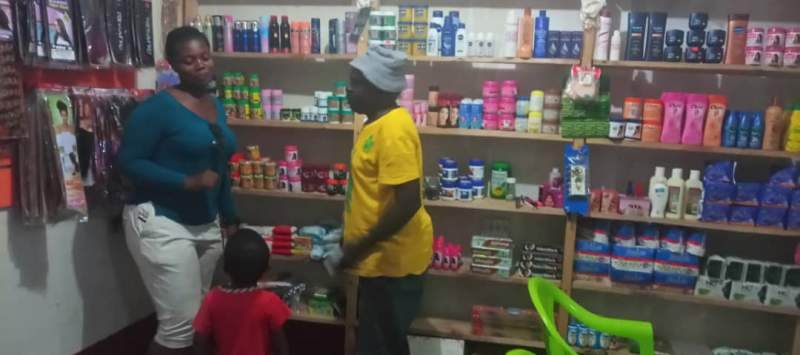 Woman stood with man and child in a shop.