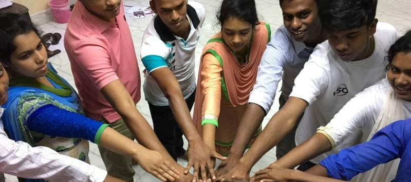 Group of people in Bangladesh in a circle with their hands touching