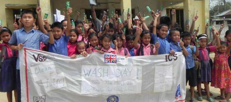 Bangladeshi children hold a banner for a WASH day