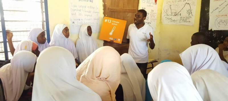 A boy in front of a classroom teaching girls about the sustainable development goals