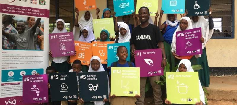 A group of school children holding signs describring the SDGs