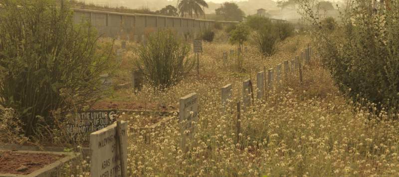 A grave of an Ebola victim lies next to weeds and plants growing in an impromptu cemetery