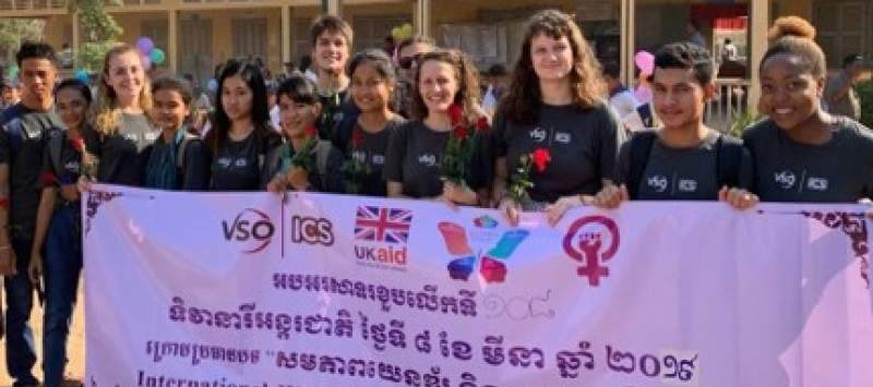 group of volunteers standing in front of a school holding a banner with cambodian writing
