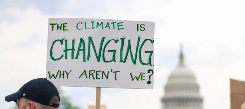 Man at protest holding sign saying: The climate is changing, why aren't we?