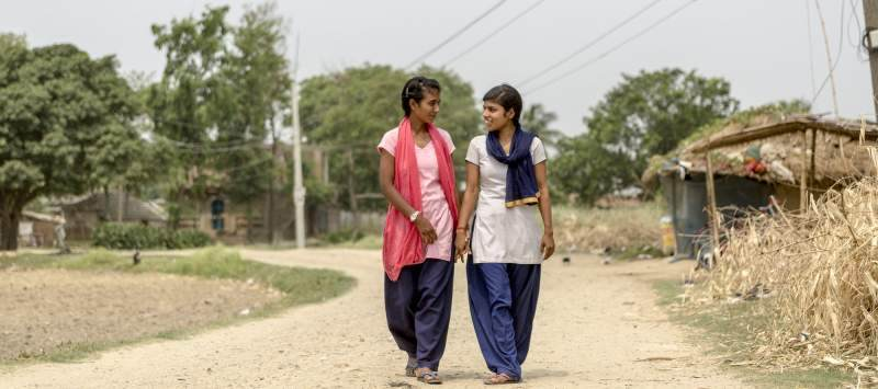 Two girls walk holding hands down a dusty empty road