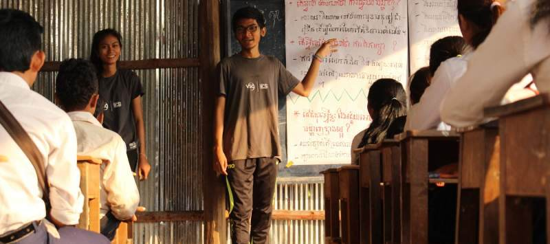 A Cambodian volunteer stands at the front of a classroom