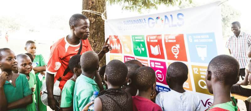 An ICS volunteers speaks to a group of children about the SDGs