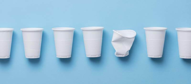 Seven plastic cups lined up against blue background, with one of them crushed
