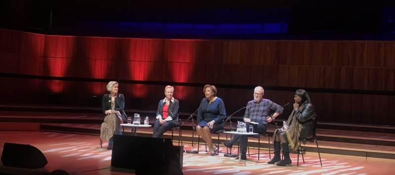 a group of people sat on a large stage as part of a panel discussion