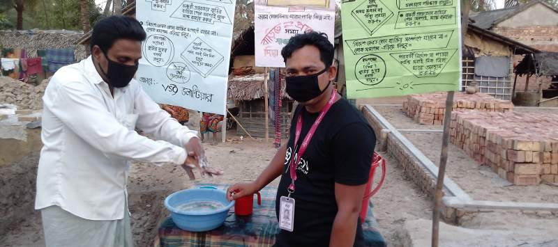 two people in bangladesh, wearing masks and washing their hands