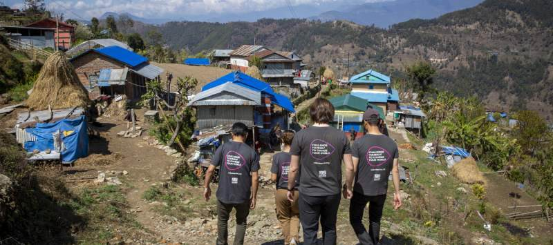 a group of ICS volunteers walking down a hill in rural nepal