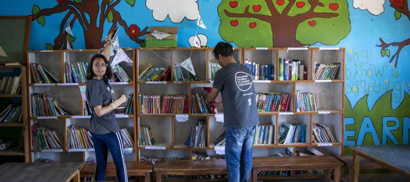 two volunteers stood in a school library