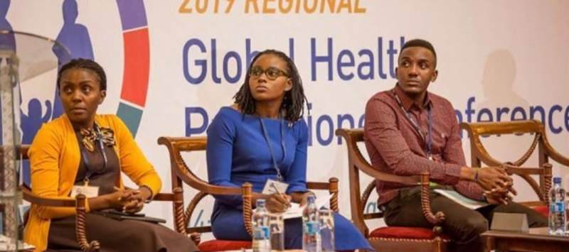 ICS alumnus Innocent sits on stage with two women at a sexual and reproductive health conference