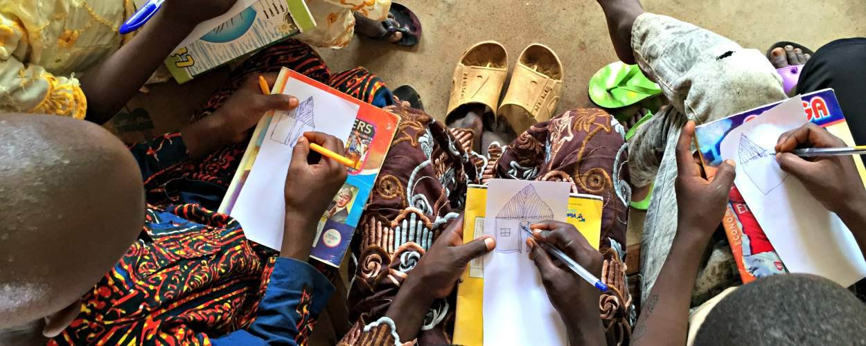 Nigerian schoolgirls draw their homes during a session by VSO ICS volunteers