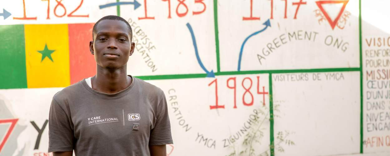Volunteer Prospere Sagna stands in front of a mural painted by ICS volunteers at Ziguinchor YMCA, Senegal