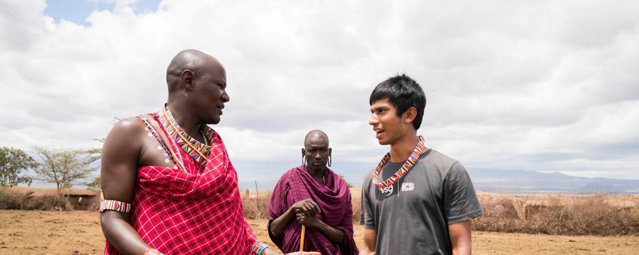 Naseem Haque volunteered abroad in Kenya. Pictured speaking with Maasai chief Benson Meoli