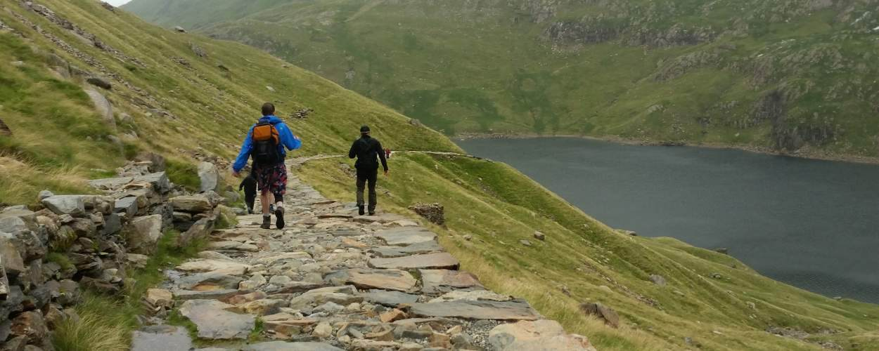 3 Volunteers walking up a mountain as part of their 3 peaks challenge.